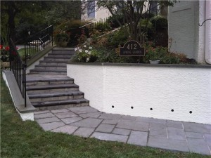 The finished project: new walkway, wall with drainage holes and new stucco